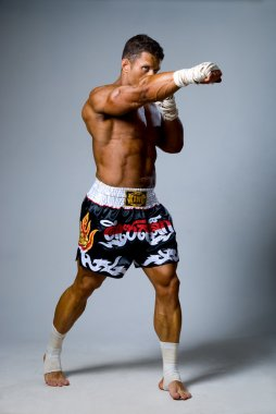Experienced adult fighter punches during training. Kickboxing