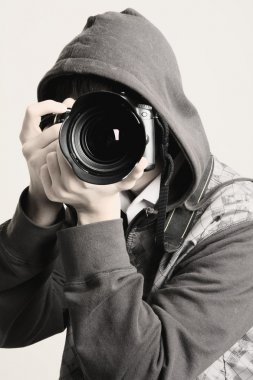 A young man in a hood using a professional camera