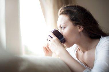 Asian girl drinking tea at the window