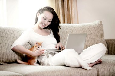 Young asian woman lies on the red sofa with red cat and working laptop
