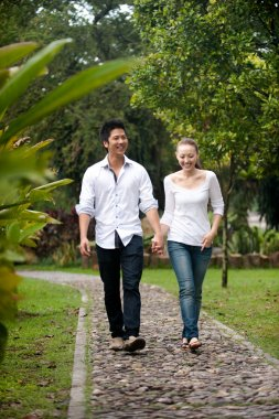 Asian couple holding hands walking on the park path