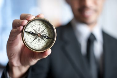 Businessman holding a compass