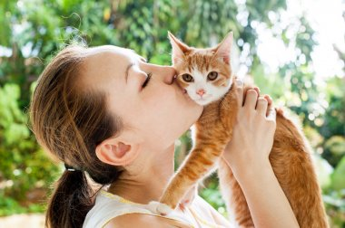 Asian woman kissing cat