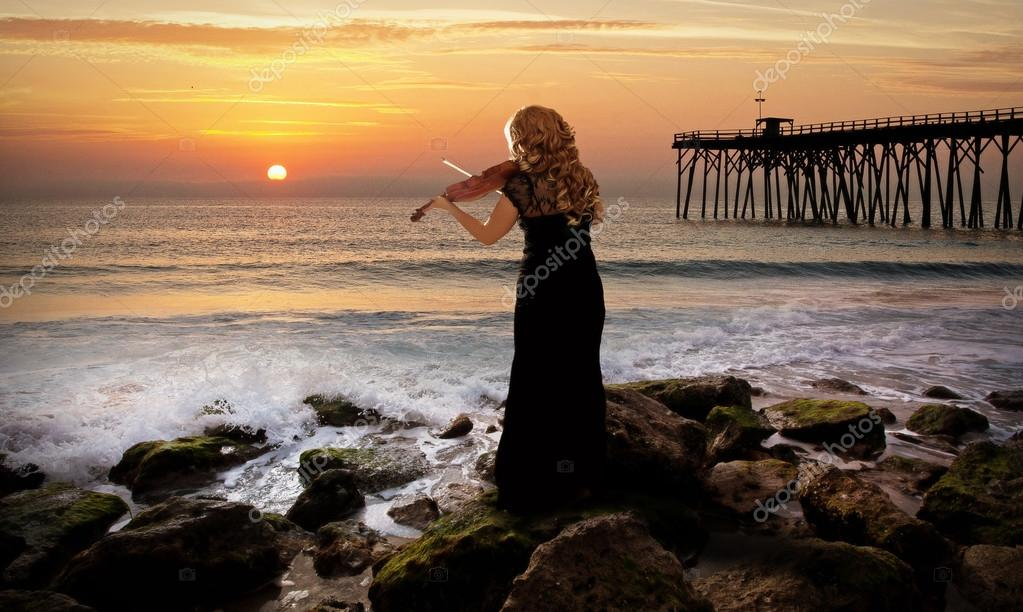 Fantasy scene with woman holding a violin at the ocean.