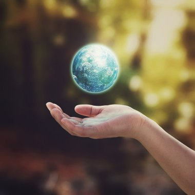 Earth floating in the air and hand