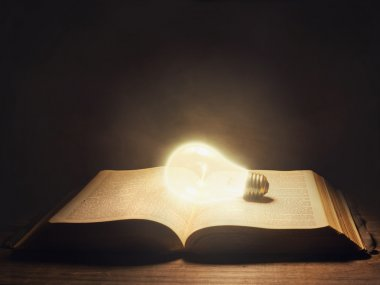 Bible with light bulb