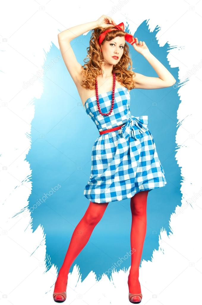 17b70206243c3 Pretty sexy redhead Pin Up girl in a checkered dress and red stockings  adjusts the bow