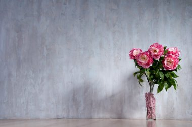Bouquet of peonies in a vase against a blue wall. Interior.