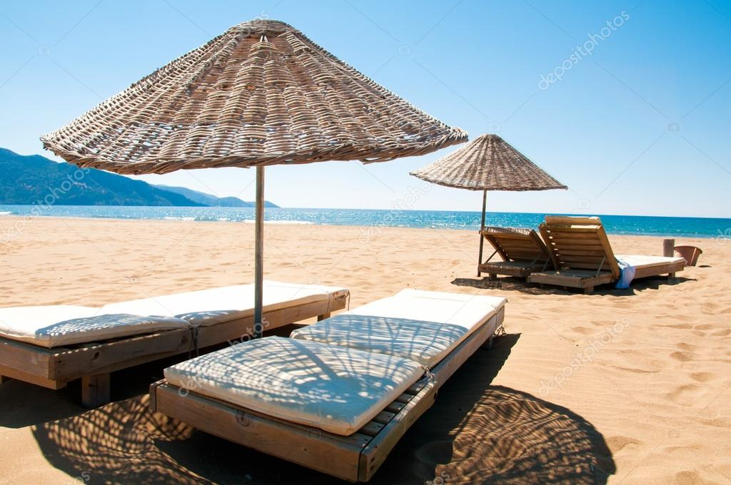Sunbeds and rattan parasols on sandy seaside.