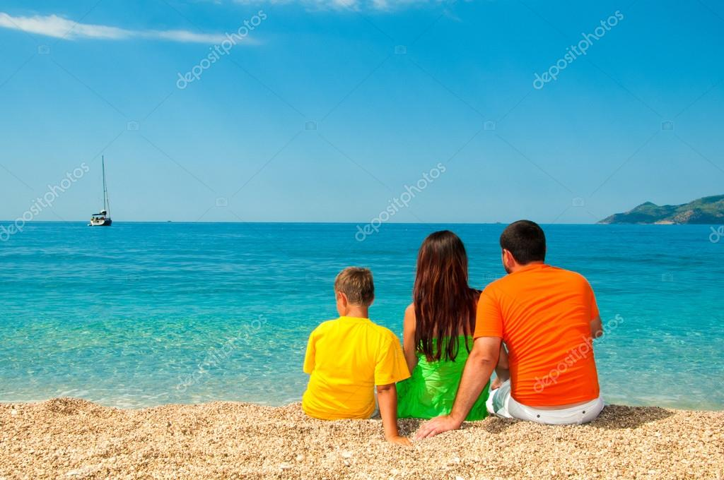 Happy family: Mom, Dad and son sitting on the beach, looking into distance
