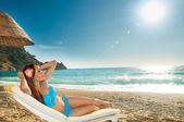 Fotografie schöne Brünette Mädchen Sonnen auf einer Liege am Meer