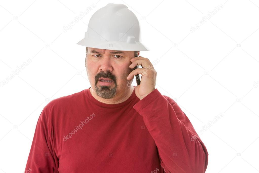 Workman looking confused talking on a mobile