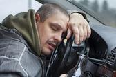 opilý muž ležící na volantu