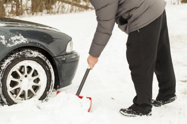 Man digging car out of the snow