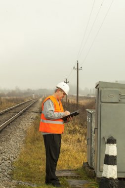 Railroad employee writes near the electrical enclosure