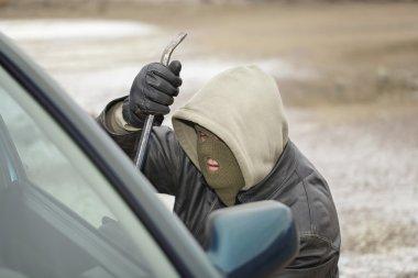 Robber trying to break open the car door