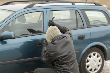 Robber with a crowbar trying to open the car door