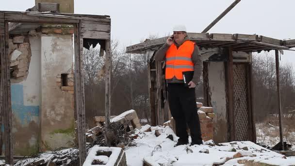 inženýr mluví po telefonu v blízkosti hořel dům