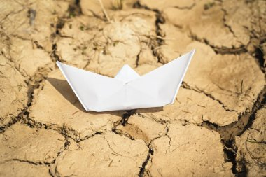 Paper boat on dry land