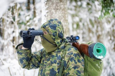 Hunter with binoculars and optical rifle in woods