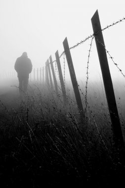 Man walking near barbed wire fence in dense fog stock vector