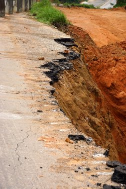 Side of the broken asphalt road collapsed and fallen, since the
