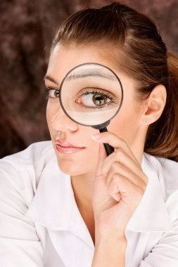 researcher looking through magnifier glass