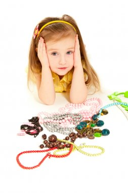 Little girl with a lot of jewel lying on the floor isolated
