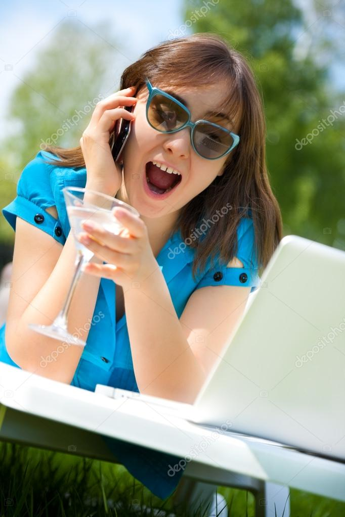 Businesswoman with laptop and glass of martini