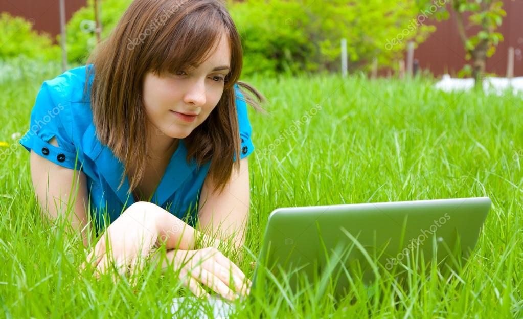 Woman with laptop lying on the grass
