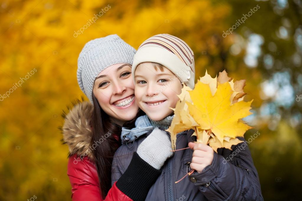 Happy Mom and son on a yellow autumn park background