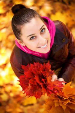 Girl on a background of autumn leafs. top view