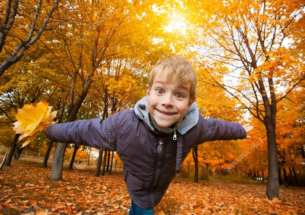 Cheerful kid on a background of sky and autumn trees