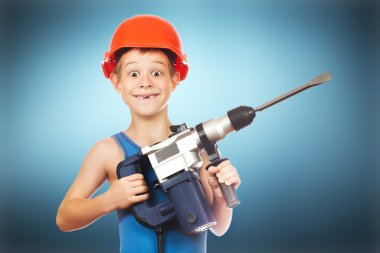Little boy in a helmet with electric hammer