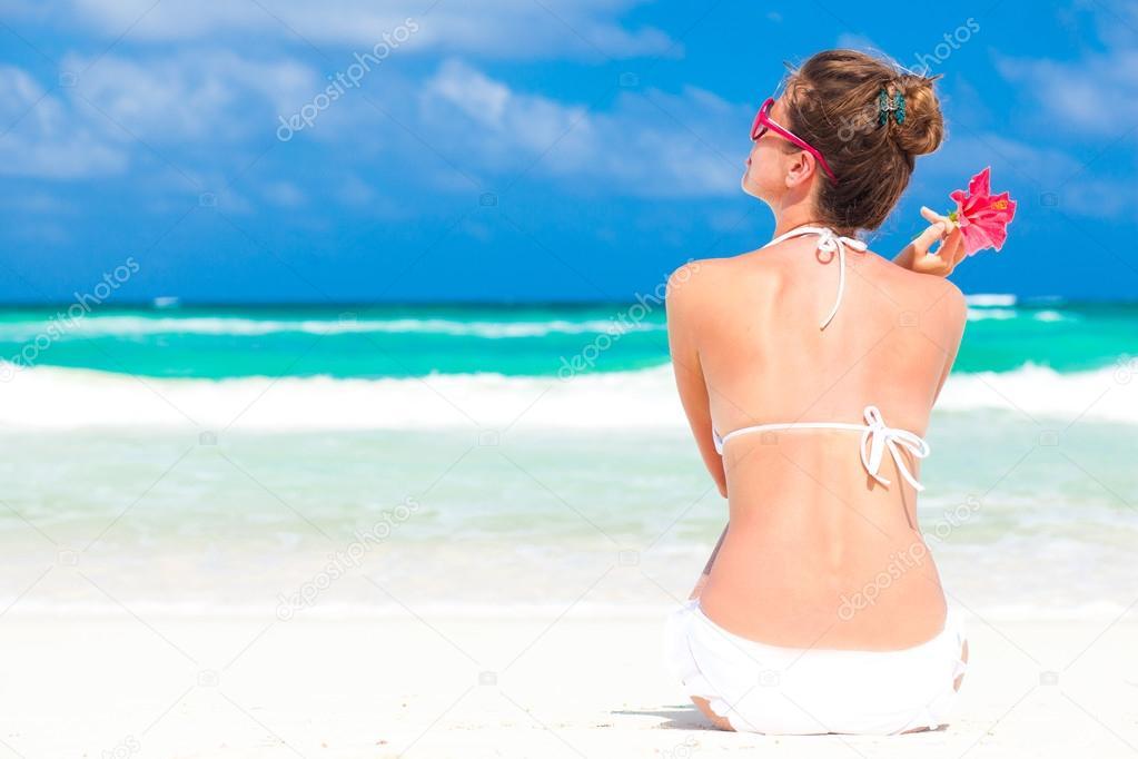 Beautiful woman in white bikini on the beach. Back view