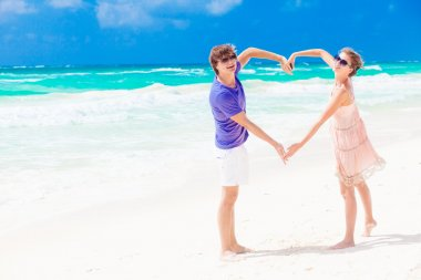 Young happy couple on honeymoon making heart shape on tropical beach