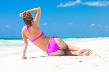 Back view of long haired young woman in bikini lying on tropical beach