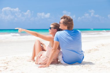 Front view happy young couple in bright clothes in sunglasses lying on beach