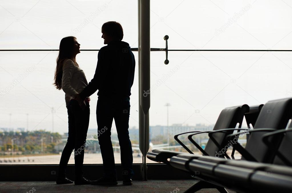 Silhouette of a couple holding hands, looking at each other and waiting at airport terminal