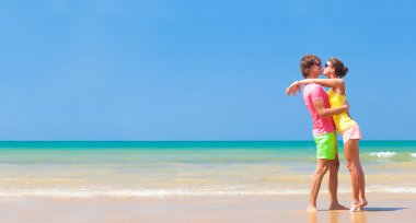 Panoramic view of happy young couple in sunglasses in bright clothes flirting on tropical beach