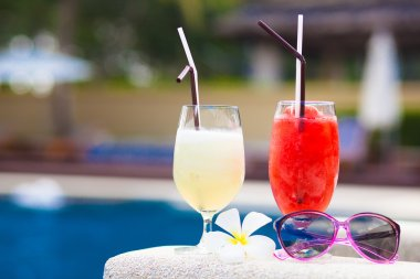 Two glasses of cocktails and sunglasses near pool