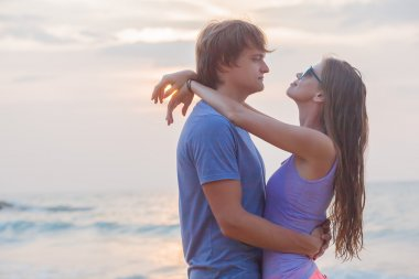 Portrait of happy young couple in love on tropical beach in the evening