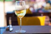 ビーチそばのテーブルに冷やした白ワインのガラス