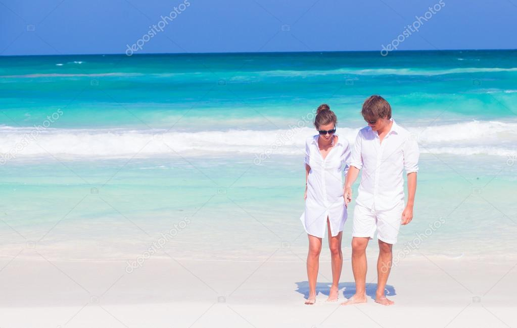 Front View Of Happy Young Couple In White Clothes And Sunglasses Having Fun At Tropical Beach