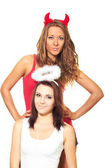 Fotografia due ragazze attraenti vestite da angeli e diavoli
