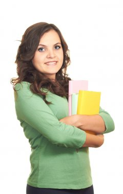 Attractive smiling girl in green shirt holding a colorful book.