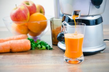 Juicer and carrot juice. Fruits in background stock vector
