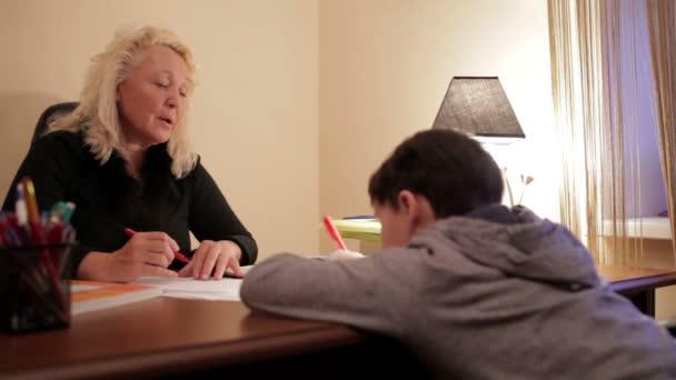 Linkshänder 12-jähriger Schüler macht die Übungen und reicht sie dem Lehrer zur Begutachtung.
