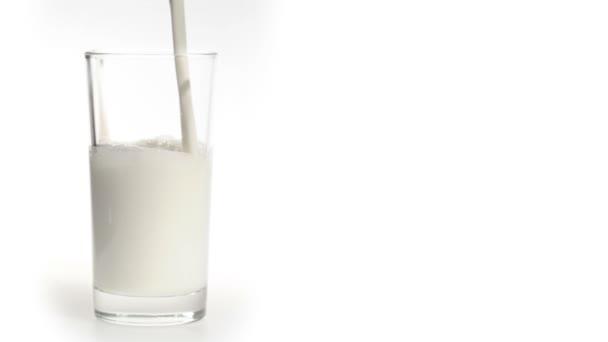 mléko proudí ve skle na bílém pozadí
