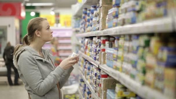 mladá žena je výběr potravin pro své dítě v nákupním centru